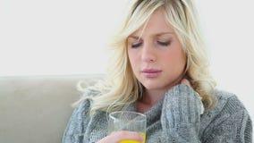 Chora młoda kobieta pije sok pomarańczowego zbiory