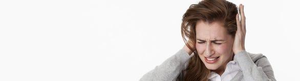 Chora młoda kobieta przy tinnitus lub słuchaniem głośna muzyka fotografia royalty free