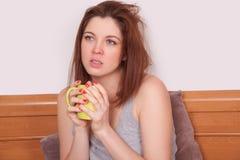 Chora młoda kobieta trzyma filiżankę herbata z czerwonym nosem Fotografia Stock