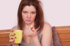 Chora młoda kobieta trzyma filiżankę herbata z czerwonym nosem Zdjęcie Royalty Free