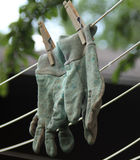 Chore gloves hanging on clothes line. Gardening or chore gloves hanging on a clothes line in summer to dry royalty free stock photos