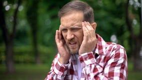 Chore mężczyzny masowania świątynie, cierpienie od migreny, ostry ból, neurologia obrazy stock