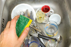 Chores, washing dishes in the sink sponge hand Royalty Free Stock Photo