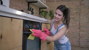 Chores, young housekeeper female in rubber gloves for cleaning wipe dusty furniture. On cuisine stock video