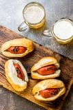 Choripan 拉丁美洲的阿根廷和智利食物 烤加调料的口利左香肠香肠热狗服务用啤酒,顶视图,石头 库存图片