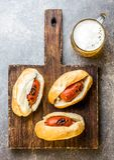 Choripan 拉丁美洲的阿根廷和智利食物 烤加调料的口利左香肠香肠热狗服务用啤酒,顶视图,石头 免版税库存照片