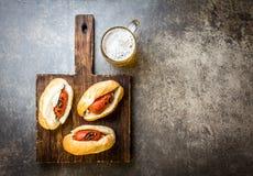 Choripan 拉丁美洲的阿根廷和智利食物 烤加调料的口利左香肠香肠热狗服务用啤酒,顶视图,石头 免版税库存图片