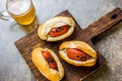 Choripan 拉丁美洲的阿根廷和智利食物 烤加调料的口利左香肠香肠热狗服务用啤酒,顶视图,石头 库存照片