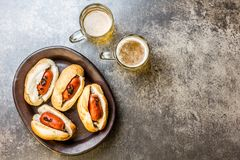Choripan. Latin American Argentine and chilean food. Grilled chorizo sausages hot dogs served with beer, top view, stone. Choripan. Latin American Argentine and royalty free stock image