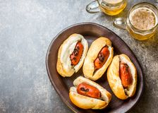 Choripan. Latin American Argentine and chilean food. Grilled chorizo sausages hot dogs served with beer, top view, stone. Choripan. Latin American Argentine and stock photos