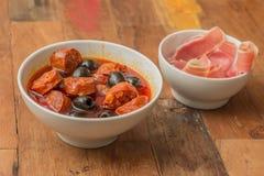Chorizo al cava with black olives Stock Photography