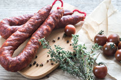 Chorizo with cherry tomatoes. On the wooden board Royalty Free Stock Photos