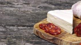 Chorizo de saucisse, tomates, ampoule d'ail et un morceau de petit fromage de brie sur le bureau en bois banque de vidéos