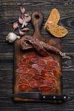 Chorizo, Messer, Stücke der Wurst, Knoblauch und Brot Beschneidungspfad eingeschlossen Stockfoto
