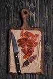 Chorizo och kniv på skärbräda Top beskådar Arkivfoto
