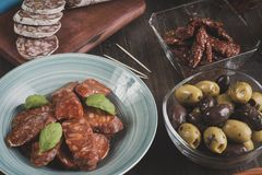 Chorizo, salami and olives on wooden table stock image