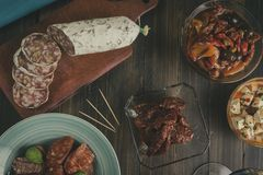 Chorizo, salami and olives on wooden table royalty free stock image