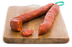 Chorizo sausage sliced on wood chopping board Stock Photos
