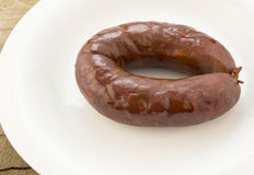 Chorizo sausage whole on white plate Royalty Free Stock Photos