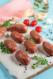 Chorizo sausages with bay leaves and tomatoes. Raw chorizo sausages with bay leaves, pepper and tomatoes Royalty Free Stock Photography