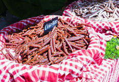 Chorizo sausages on red checked cloth in French market in Paris, France Royalty Free Stock Image