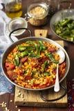 Chorizoen och gula torkade delade ärtor låter småkoka med padronpeppar och tomater royaltyfria bilder