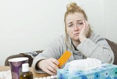 Choroba, smucenie i zmęczonej kobiety siedzący mienie, pastylka i leki Ogromna migrena zdjęcia stock