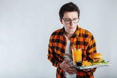Choroba smutny młody człowiek w koszula stawia rękę na bólowym podbrzusza, obolałości, pozycji i mienia hamburgerze odizolowywają zdjęcia stock