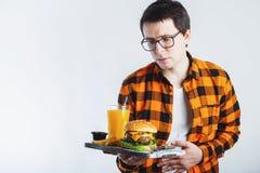 Choroba smutny młody człowiek w koszula stawia rękę na bólowym podbrzusza, obolałości, pozycji i mienia hamburgerze odizolowywają fotografia stock