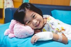 Choroby azjatykci dziecko przyznawa? w szpitalu z zasolonym iv kapinosem na r?ce Opiek zdrowotnych opowie?ci zdjęcie stock