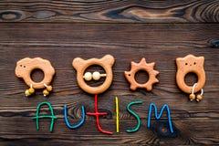 choroby Infantylny autyzm Słowo z barwionych listów pobliskimi zabawkami na ciemnego drewnianego tło odgórnego widoku tła odgórny obraz stock