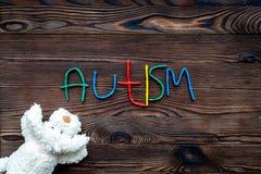 choroby Infantylny autyzm Słowo z barwionych listów pobliskimi zabawkami na ciemnego drewnianego tło odgórnego widoku tła odgórny zdjęcie royalty free