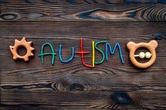 choroby Infantylny autyzm Słowo z barwionych listów pobliskimi zabawkami na ciemnego drewnianego tło odgórnego widoku tła odgórny zdjęcie stock