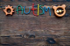 choroby Infantylny autyzm Słowo z barwionych listów pobliskimi zabawkami na ciemnego drewnianego tło odgórnego widoku tła odgórny fotografia royalty free