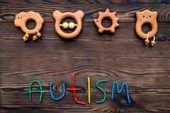choroby Infantylny autyzm Słowo z barwionych listów pobliskimi zabawkami na ciemnego drewnianego tło odgórnego widoku tła odgórny zdjęcia stock