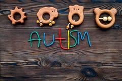choroby Infantylny autyzm Słowo z barwionych listów pobliskimi zabawkami na ciemnego drewnianego tło odgórnego widoku tła odgórny obrazy stock