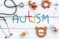 choroby Infantylny autyzm Słowo z barwionych listów pobliskimi zabawkami, stetoskop, pigułki na białego drewnianego tła odgórnym  obraz stock