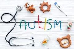 choroby Infantylny autyzm Słowo z barwionych listów pobliskimi zabawkami, stetoskop, pigułki na białego drewnianego tła odgórnym  obrazy royalty free