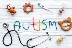 choroby Infantylny autyzm Słowo z barwionych listów pobliskimi zabawkami, stetoskop, pigułki na białego drewnianego tła odgórnym  zdjęcie royalty free