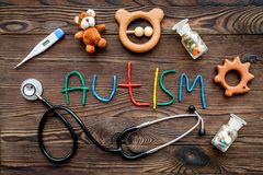 choroby Infantylny autyzm Słowo z barwionych listów pobliskimi zabawkami, stetoskop, pigułki na ciemnego drewnianego tła odgórnym obrazy royalty free
