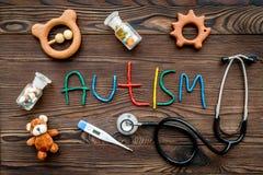 choroby Infantylny autyzm Słowo z barwionych listów pobliskimi zabawkami, stetoskop, pigułki na ciemnego drewnianego tła odgórnym zdjęcia stock