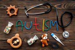 choroby Infantylny autyzm Słowo z barwionych listów pobliskimi zabawkami, stetoskop, pigułki na ciemnego drewnianego tła odgórnym fotografia royalty free