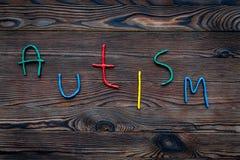 choroby Infantylny autyzm Słowo z barwionymi listami na ciemnym drewnianym tło odgórnego widoku tła odgórnego widoku copyspace fotografia stock