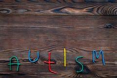 choroby Infantylny autyzm Słowo z barwionymi listami na ciemnym drewnianym tło odgórnego widoku tła odgórnego widoku copyspace obrazy royalty free
