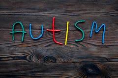 choroby Infantylny autyzm Słowo z barwionymi listami na ciemnym drewnianym tło odgórnego widoku tła odgórnego widoku copyspace zdjęcia royalty free