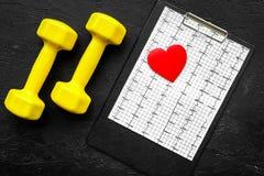 choroby serca uniemożliwia Serca znak, kardiogram i dumbbells na czarnego tła odgórnym widoku, Zdjęcie Stock