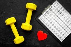 choroby serca uniemożliwia Serca znak, kardiogram i dumbbells na czarnego tła odgórnym widoku, Fotografia Stock