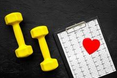 choroby serca uniemożliwia Serca znak, kardiogram i dumbbells na czarnego tła odgórnym widoku, Obrazy Stock