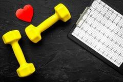 choroby serca uniemożliwia Serca znak, kardiogram i dumbbells na czarnym tło odgórnego widoku copyspace, Zdjęcia Stock