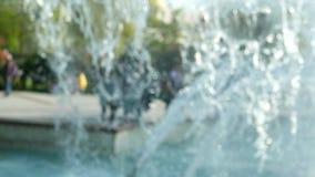 Chorro de agua de la fuente de la ciudad en un fondo borroso con la gente que camina alrededor de las fuentes en el centro de ciu almacen de metraje de vídeo